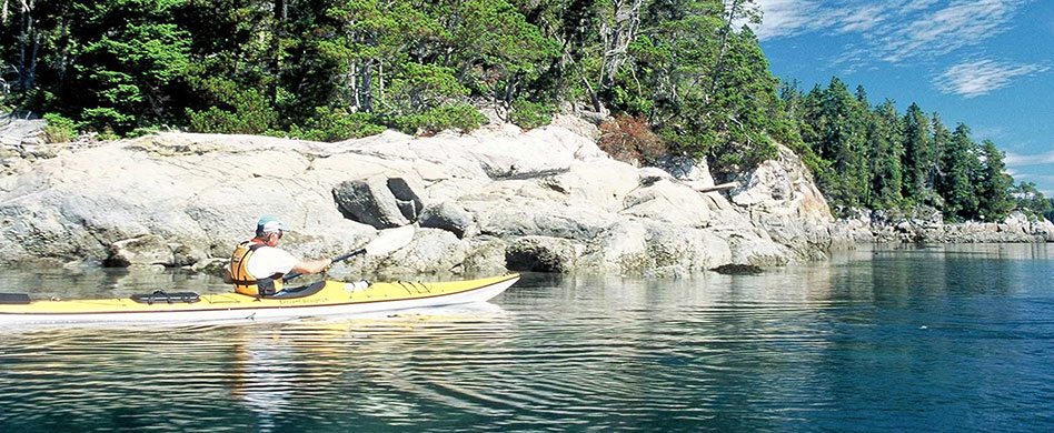 sea kayaker along shoreline rocks